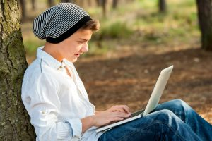 Portrait of teen boy chatting on laptop in park.